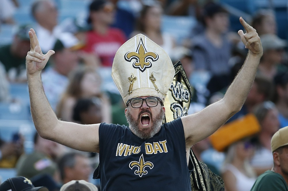 A New Orleans Saints fan cheers during the second half of an NFL football game between the New Orleans Saints and the Green Bay Packers, Sunday, Sept. 12, 2021, in Jacksonville, Fla. (AP Photo/Stephen B. Morton)