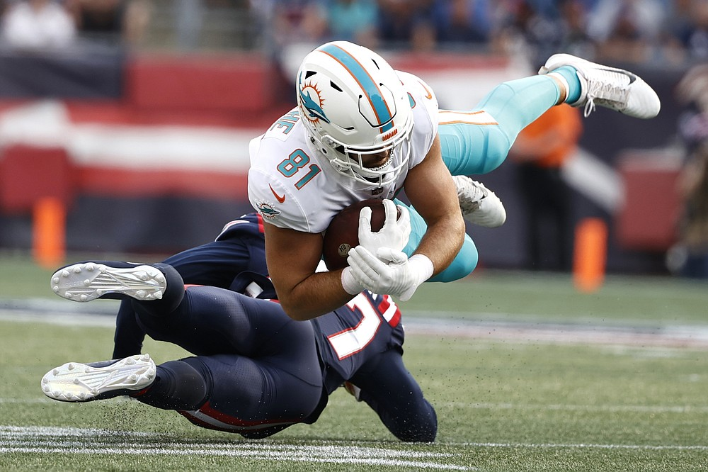 Miami Dolphins tight end Durham Smythe (81) hangs onto the ball while taken down by New England Patriots defensive back J.C. Jackson during the first half of an NFL football game, Sunday, Sept. 12, 2021, in Foxborough, Mass. (AP Photo/Winslow Townson)