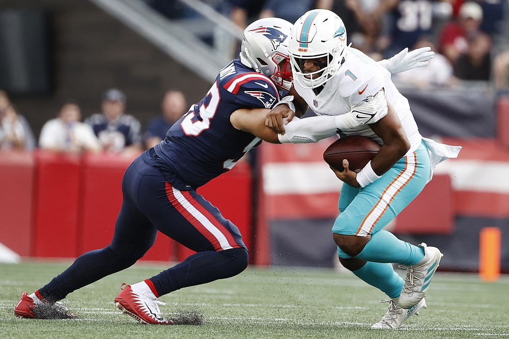 New England Patriots middle linebacker Kyle Van Noy, left, takes down Miami Dolphins quarterback Tua Tagovailoa, right, during the first half of an NFL football game, Sunday, Sept. 12, 2021, in Foxborough, Mass. (AP Photo/Winslow Townson)