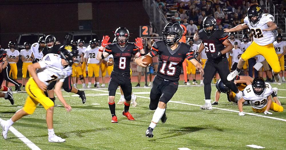 Sophomore quarterback Gavin Dixon, No. 15, evades Tiger defenders Friday, Sept. 10, 2021, as he makes a run.