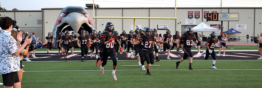 The Pea Ridge Blackhawk football team enters the stadium cheered by Blackhawk cheerleaders Friday, Sept. 10, 2021.