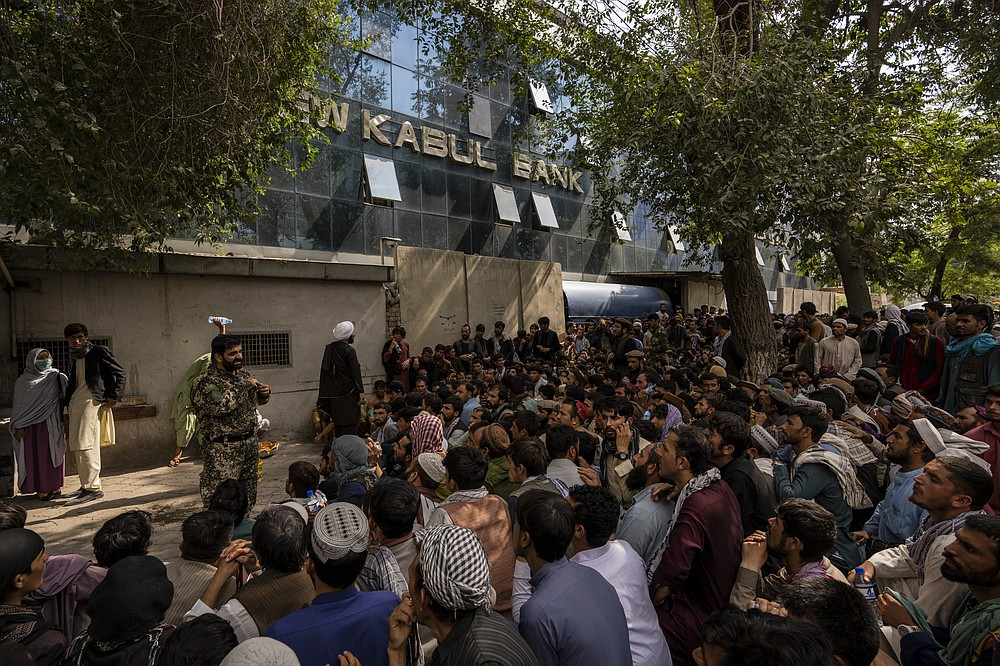 Afghans wait in front of a bank as they try to withdraw money in Kabul, Afghanistan, Sunday, Sept. 12, 2021. (AP Photo/Bernat Armangue)