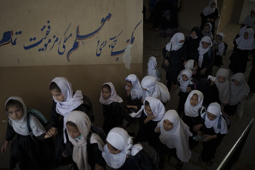 Girls walk upstairs as they enter a school before class in Kabul, Afghanistan, Sunday, Sept. 12, 2021. (AP Photo/Felipe Dana)