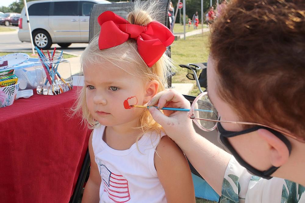 LYNN KUTTER ENTERPRISE-LEADER Ray Murphy of Farmington set up a faceprinting booth Saturday at the Farmington Fall Festival. Layden Abrecht, 2, of Farmington, takes her turn for a pumpkin on her cheek.