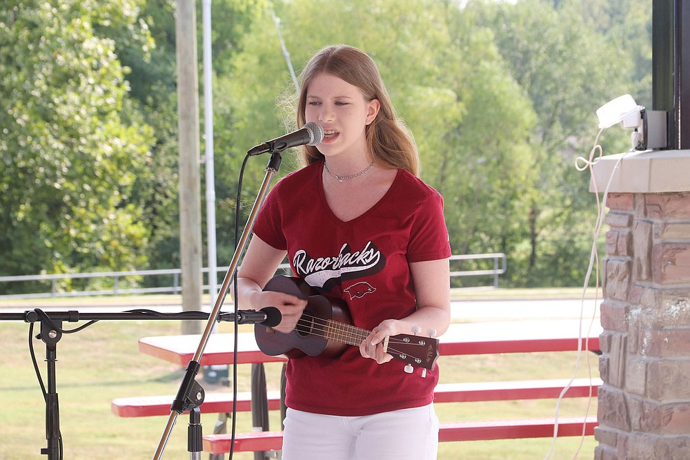 Emily Draper, a student at Inside Out Studio in Farmington, plays and sings with the ukulele at the Farmington Fall Festival on Saturday. She also sang during the ceremony to commemorate 9-11.