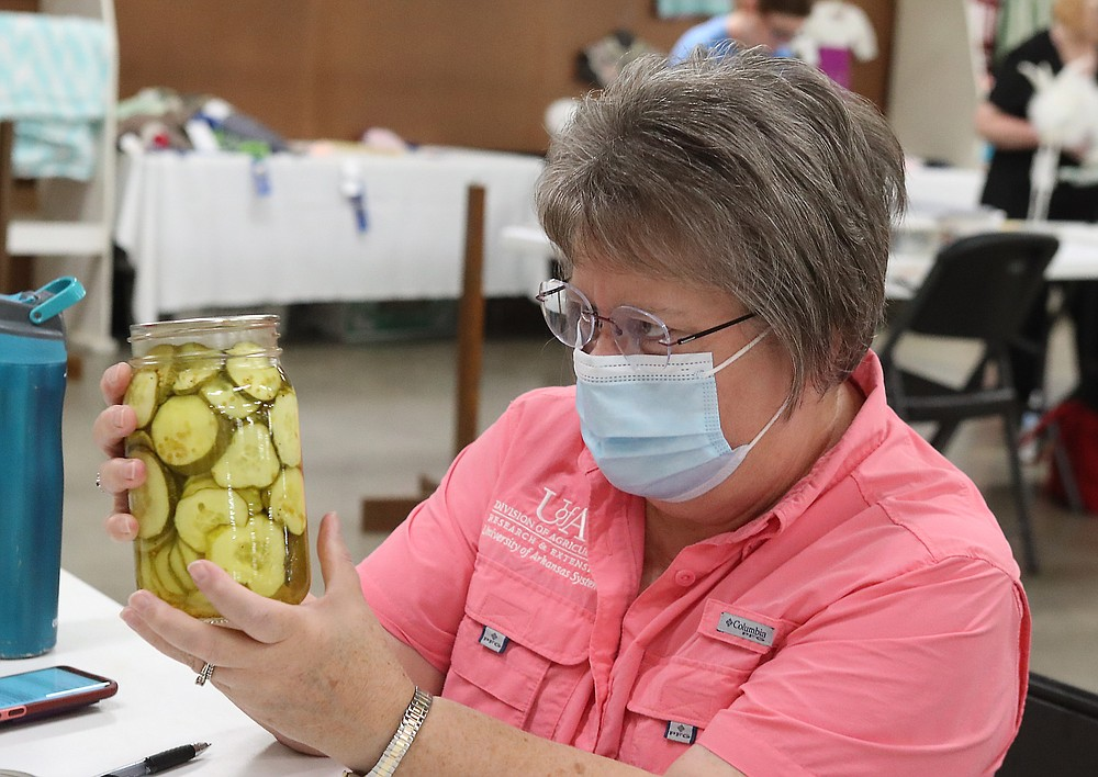 Judge Jean Ince looks over a jar of pickles during the Creative Arts judging at the Garland County Fair Monday. - Photo by Richard Rasmussen of The Sentinel-Record