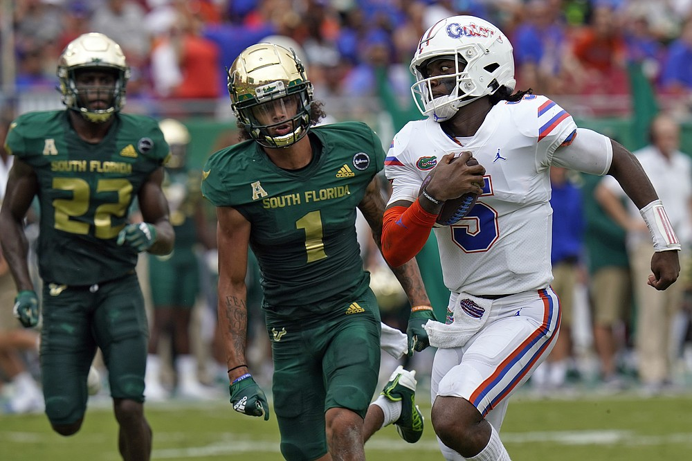Florida quarterback Emory Jones (5) outruns South Florida defensive back Mekhi LaPointe (22) and safety Matthew Hill (1) on a 33-yarad touchwon run during the first half of an NCAA college football game Saturday, Sept. 11, 2021, in Tampa, Fla. (AP Photo/Chris O'Meara)