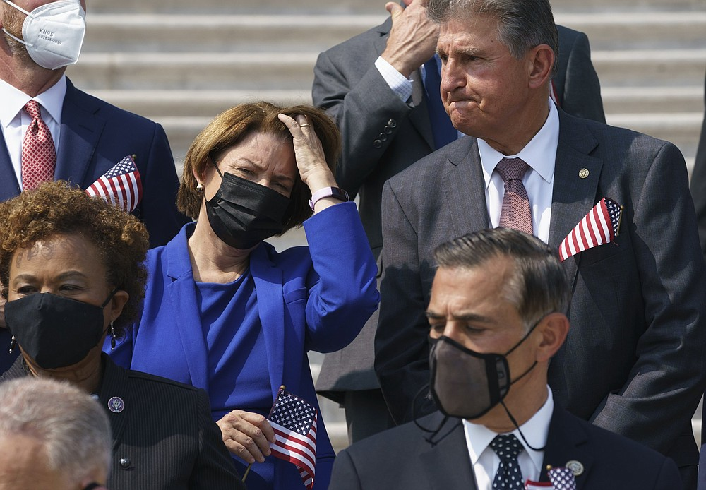 Sen. Amy Klobuchar, D-Minn., left, and Sen. Joe Manchin, D-W.Va., stand on the steps of the Capitol during a Sept. 11 remembrance ceremony, in Washington, Monday, Sept. 13, 2021. As congressional Democrats speed ahead this week in pursuit of President Joe Biden's $3.5 trillion plan for social and environmental spending, Manchin, a Democratic senator vital to the bill's fate, says the cost will need to be slashed to $1 trillion to $1.5 trillion to win his support. (AP Photo/J. Scott Applewhite)
