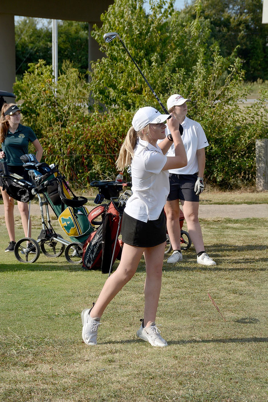 Graham Thomas/Herald-Leader Siloam Springs golfer Baylee Morris watches after she hits a tee shot as teammate Brooke Smith looks on during Monday's match at The Course at Sager's Crossing.