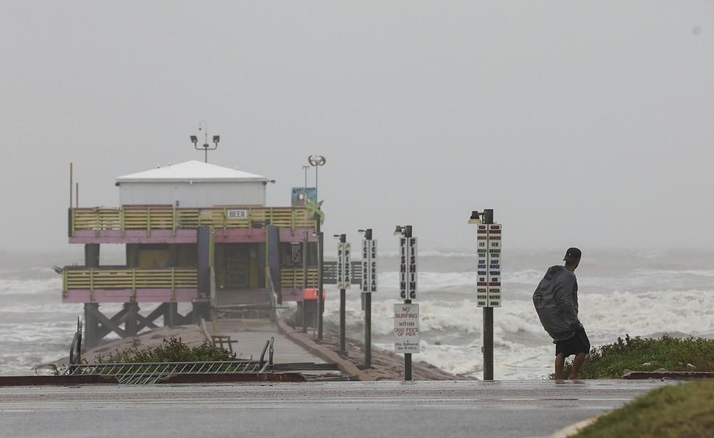 A man walks down Seawall Boulevard near 61st Street on Tuesday, Sept. 14, 2021, in Galveston, Texas. Hurricane Nicholas made landfall early in the morning along the coast. (Jon Shapley/Houston Chronicle via AP)