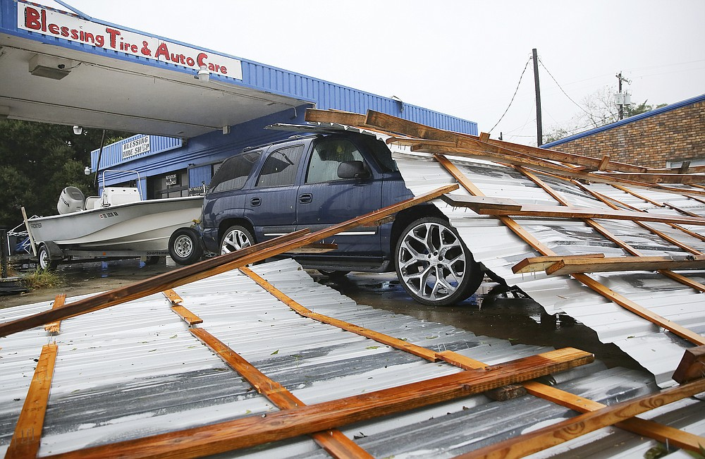Parts of a roof sit on top of a car parked at Blessings Tire and Auto Care following Hurricane Nicholas in Bay City, Texas on Tuesday, Sept. 14, 2021. According to the owner of the business, he wasn't sure where the roof came from. (Elizabeth Conley/Houston Chronicle via AP)