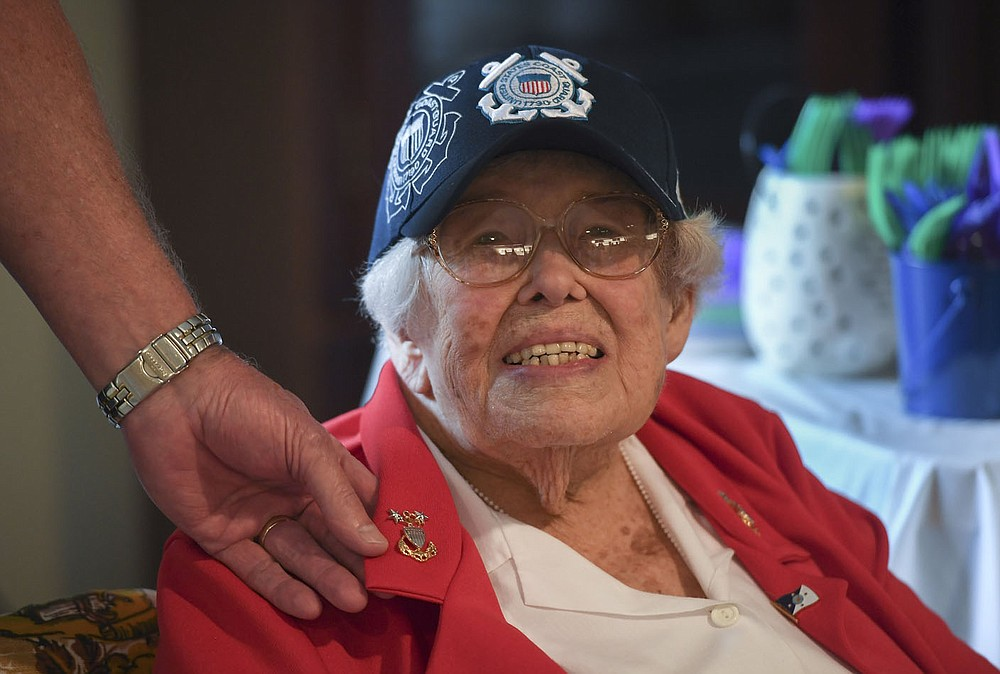 """Rick Trent, retired MCPOCG, shows the Honorary Master Chief Petty Officer rank emblem pinned on the collar of Lois Bouton (center), Thursday, September 16, 2021 at the Innisfree Assisted Living in Rogers. 102 year old Lois Bouton is known as """"The Coast Guard Lady"""". She received the Spirit of Hope Medal from the Department of Defense and Pentagon Thursday at her retirement community home. Check out nwaonline.com/210919Daily/ for today's photo gallery.  (NWA Democrat-Gazette/Charlie Kaijo)"""