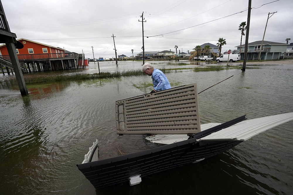 Jeff Geno takes apart a damaged storage unit in the aftermath of Hurricane Nicholas Tuesday, Sept. 14, 2021, in Surfside Beach, Texas. (AP Photo/David J. Phillip)