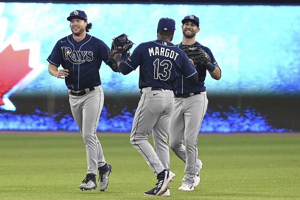Tampa Bay Ray' Austin Meadows, Manuel Margot and Kevin Kiermaier, from left, celebrate the team's win over the Toronto Blue Jays in a baseball game Tuesday, Sept. 14, 2021, in Toronto. (Jon Blacker/The Canadian Press via AP)