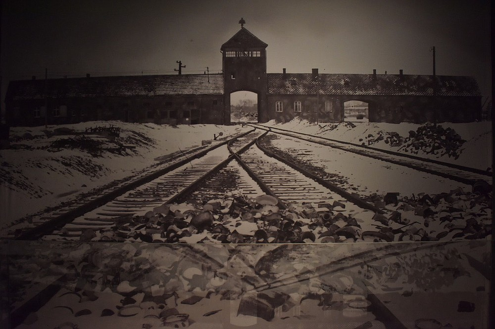 """All over the world, Auschwitz has become a symbol of terror, genocide and the Shoah. It was established by Germans in 1940, in the suburbs of the Polish city of Oswiecim and became the largest of the extermination centers where the """"Endlösung der Judenfrage"""" (the final solution to the Jewish question — the Nazi plan to murder European Jews) was carried out, according to the Auschwitz-Birkenau Memorial and Museum. This image of the main gate was taken from inside the camp after the liberation.  (Pawel Sawicki, Auschwitz Memorial)"""