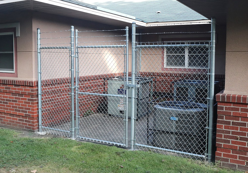 The county fenced off HVAC units at the Garland County Health Unit to keep out the homeless. - Photo by Richard Rasmussen