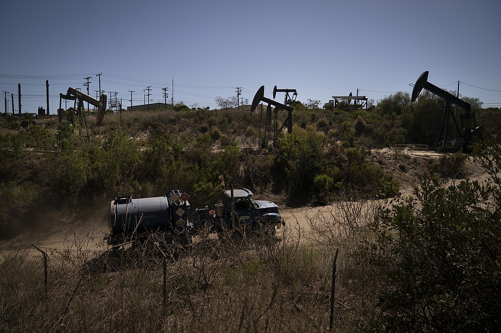 A truck drives past pump jacks operating at the Inglewood Oil Field, Thursday, June 10, 2021, in Los Angeles. (AP Photo/Jae C. Hong)
