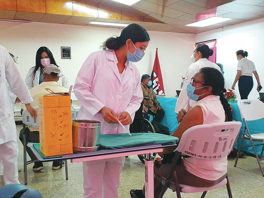 A nurse talks to a woman that is about to get inoculated with the AstraZeneca COVID-19 vaccine at the Berta Calderon hospital in Managua, Nicaragua, Thursday, April 8, 2021. Nicaragua has started the second phase of its vaccination program with 60-year-old persons now being inoculated. (AP Photo/Gabriela Selser)