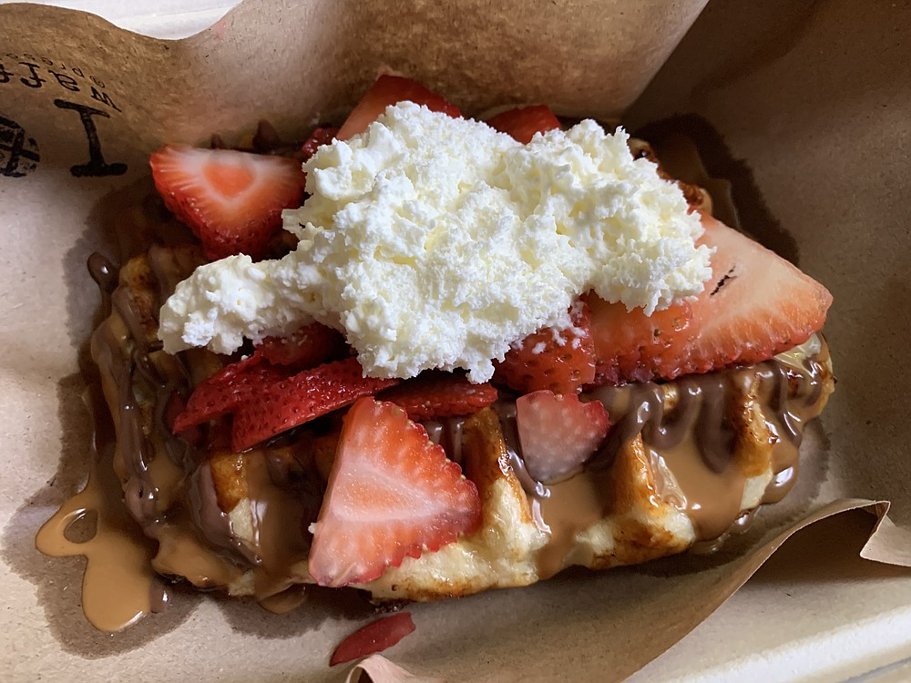 The House from Press Waffle Co. tops a liege waffle with Nutella, a cookie-dough syrup drizzle, strawberries and — to-go — a self-applied house-made whipped cream. (Arkansas Democrat-Gazette/Eric E. Harrison)