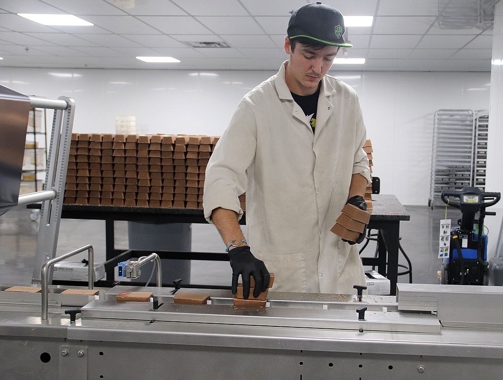 LYNN KUTTER ENTERPRISE-LEADER Layne Nikes puts Keto Savage Bars on a conveyor belt.  The company produces the keto bars at the former Harps grocery store in Lincoln.  The bars go from the conveyor belt to a machine that wraps the bars.  From there the bars are packed and shipped.
