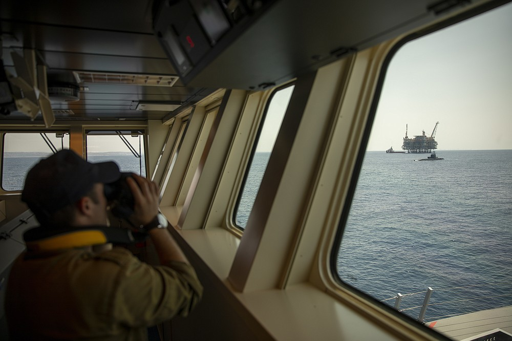 An Israeli Navy sailor looks at Israel's offshore Leviathan gas field from on board the Israeli Navy Ship Atzmaut as a submarine patrols in the Mediterranean Sea , Wednesday, Sept. 1, 2021. One of the navy's most important responsibilities is protecting Israel's natural gas platforms in the Mediterranean Sea, which now provide some 75% of the country's electricity. (AP Photo/Ariel Schalit)