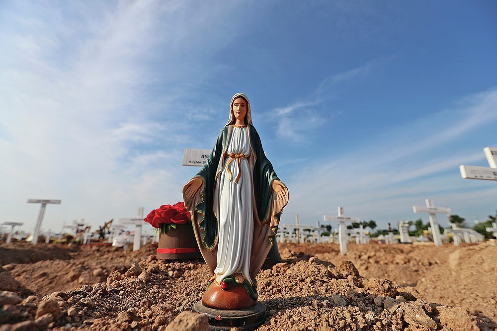 A statue of Virgin Mary is placed on the grave of a woman who died of COVID-19 at Rorotan Cemetery in Jakarta, Indonesia, Wednesday, Sept. 1, 2021. In the graveyard on Jakarta's outskirts, portraits of the dead, bouquets of flowers and other mementos serve as reminders of the deadly coronavirus wave that battered Indonesia over the summer. (AP Photo/Achmad Ibrahim)