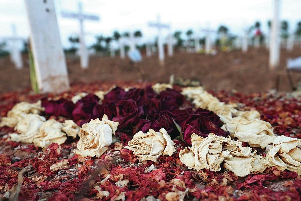 Dried flowers are seen on the grave of a COVID-19 victim at Rorotan Cemetery in Jakarta, Indonesia, Wednesday, Sept. 1, 2021. In the graveyard on Jakarta's outskirts, portraits of the dead, bouquets of flowers and other mementos serve as reminders of the deadly coronavirus wave that battered Indonesia over the summer. (AP Photo/Achmad Ibrahim)