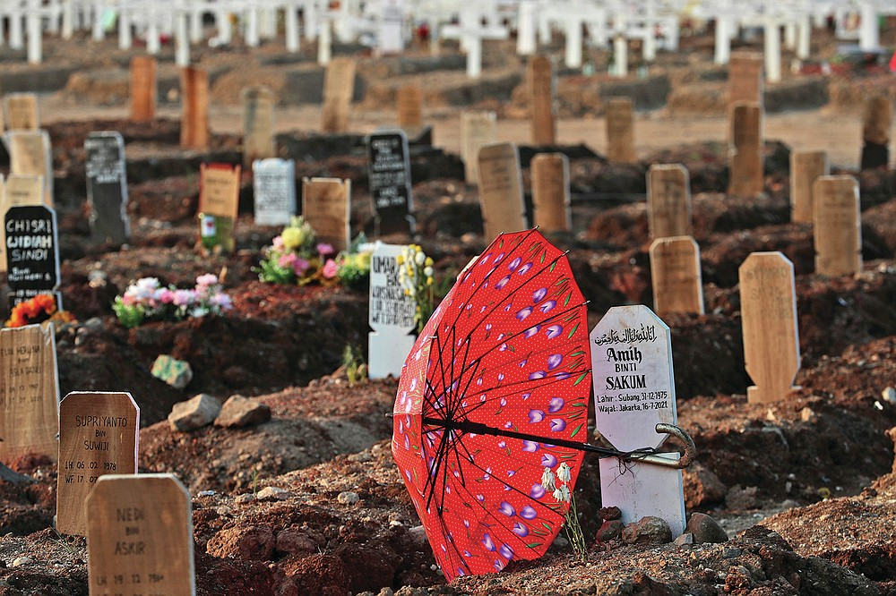 An umbrella lays at the grave of a woman who died of COVID-19 complications at Rorotan Cemetery in Jakarta, Indonesia, Wednesday, Aug. 25, 2021. In a graveyard on Jakarta's outskirts, portraits of the dead, bouquets of flowers and other mementos serve as reminders of the deadly coronavirus wave that battered Indonesia over the summer. (AP Photo/Achmad Ibrahim)
