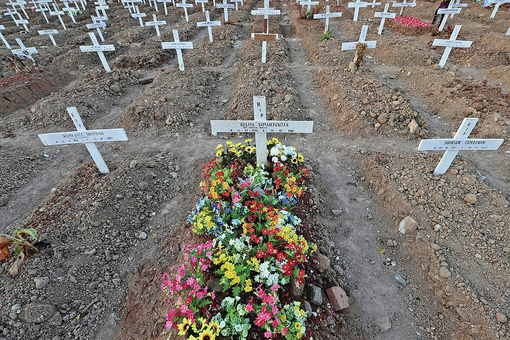 Flowers adorn a grave at Rorotan Cemetery in Jakarta, Indonesia, Wednesday, Sept. 1, 2021. In the graveyard on Jakarta's outskirts, portraits of the dead, bouquets of flowers and other mementos serve as reminders of the deadly coronavirus wave that battered Indonesia over the summer. (AP Photo/Achmad Ibrahim)