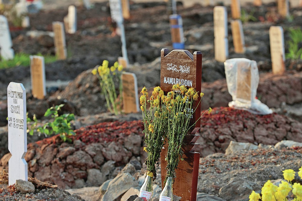 Flowers are laid on the grave of a COVID-19 victim at Rorotan Cemetery in Jakarta, Indonesia, Wednesday, Aug. 25, 2021. In the graveyard on Jakarta's outskirts, portraits of the dead, bouquets of flowers and other mementos serve as reminders of the deadly coronavirus wave that battered Indonesia over the summer. (AP Photo/Achmad Ibrahim)