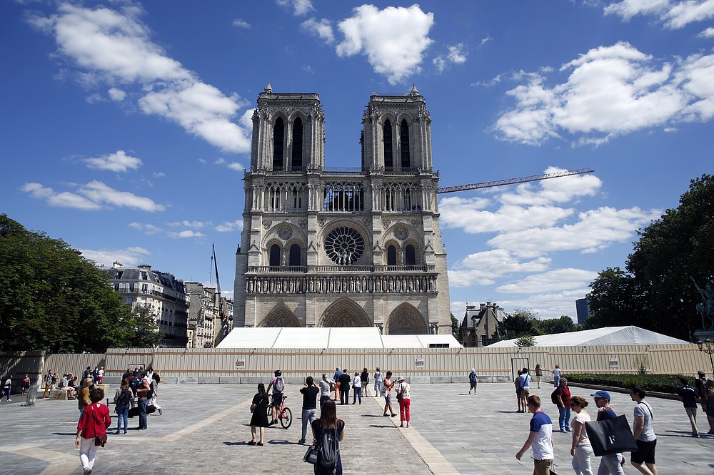 FILE - I this May 31, 2020 file photo, people walk on the forecourt of Notre Dame's Cathedral, in Paris. France's Notre Dame Cathedral is finally stable and secure enough for artisans to start rebuilding it, more than two years after the shocking fire that tore through its roof, knocked down its spire and threatened to bring the rest of the medieval monument down, too. (AP Photo/Thibault Camus, File)