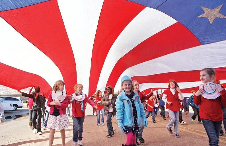 Hugh Goodwin students walk under an American flag during the school's first ever Veterans Day parade in 2012. The parade has since become an annual event the school holds. Principal Jesica Collins selected this photo to represent Hugh Goodwin in her application for the school to be recognized as a National Blue Ribbon School. (Michael Orrell/News-Times file)