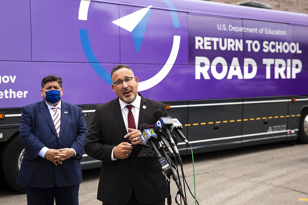"""U.S. Secretary of Education Miguel Cardona speaks as Illinois Gov. J.B. Pritzker looks on Tuesday afternoon, Sept. 21, 2021, in Cicero, Ill. Cardona announced the National Blue Ribbon Schools of 2021 during an event in Illinois as part of his """"Return to School Road Trip."""" (Ashlee Rezin/Chicago Sun-Times via AP)"""