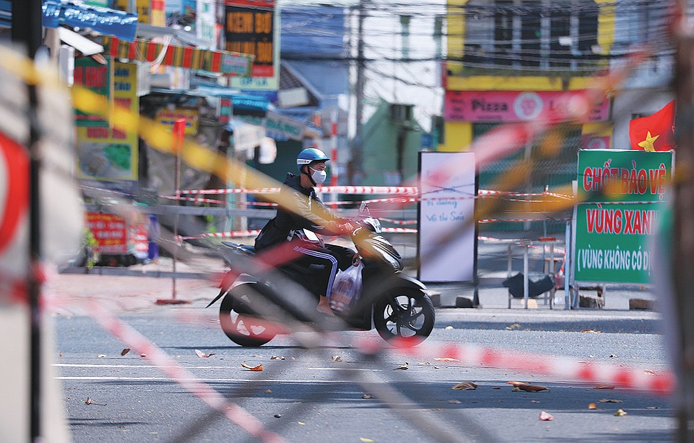 A man rides a scooter past road barricades made from scaffoldings and cordon tapes in Vung Tau, Vietnam, Monday, Sept. 20, 2021. In Vung Tau, just outside Ho Chi Minh city, streets are sealed and checkpoints are set up to control the movement of people. Barbed wire, door panels, steel sheets, chairs and tables are among materials being used to fence up alleys and isolate neighborhoods.(AP Photo/Hau Dinh)