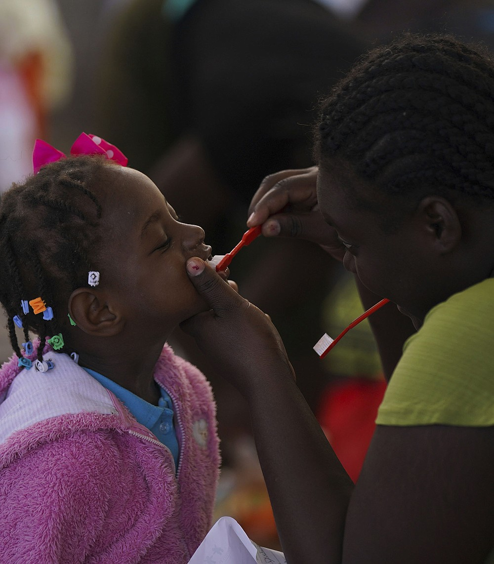 A Haitian migrant woman brushes her daughter's teeth Saturday in a shelter in Ciudad Acuna, Mexico, where authorities had moved migrants who had been cleared out of camps in Mexico and the United States. More photos at arkansasonline.com/926delrio/. (AP/Fernando Llano)