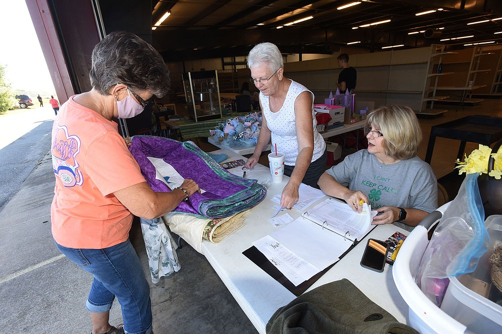 Cinda (cq) Wooldridge (left) of Pea Ridge enters her hand-made quilts on Saturday Sept. 25 2021 for judging at the Benton County Fair. Debe (cq) Greene (center) and Janice Shofner check in entries.  (NWA Demorcrat/Gazette/Flip Putthoff)