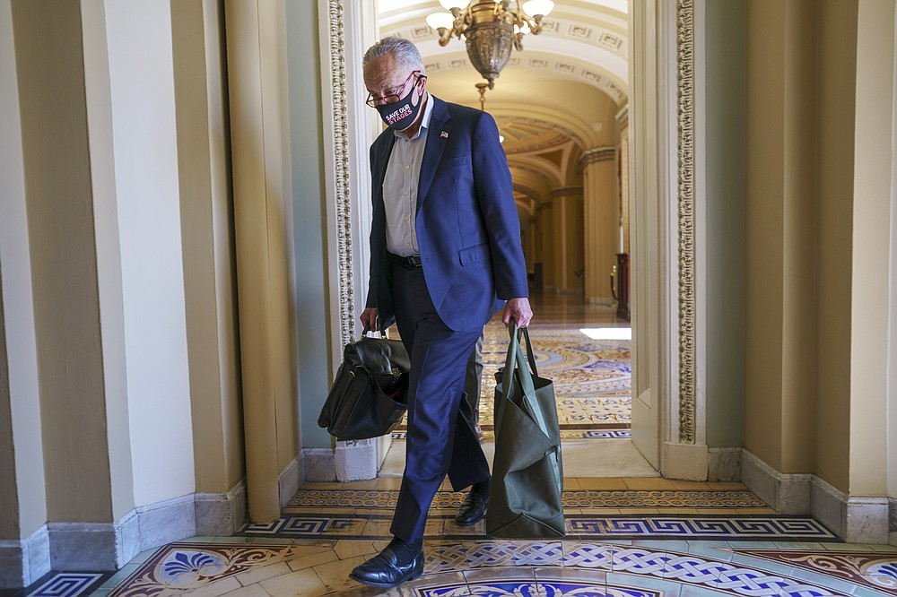 """Senate Majority Leader Chuck Schumer, D-N.Y., arrives at the Capitol as a consequential week begins for President Joe Biden's agenda and Democratic leaders in Congress who are trying to advance his $3.5 trillion """"Build Back Better"""" package and pass legislation to avoid a federal shutdown, in Washington, Monday, Sept. 27, 2021. (AP Photo/J. Scott Applewhite)"""