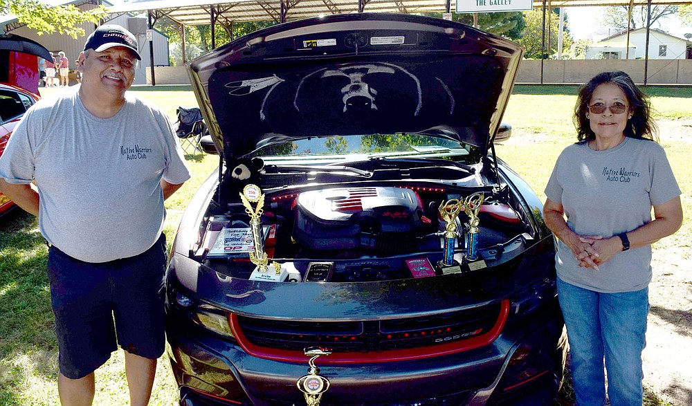 Westside Eagle Observer/MIKE ECKELS  Charles Moncooxea (left) and wife Christine show off the many awards they have earned with their Dodge Charger which was one of many custom muscle cars on display during the 2021 Veterans Park Car Show in Decatur Sept. 25. The bear on the inside of the hood sets the theme for the car which is a tribute to the Moncooxea's Native American heritage. Charles does the custom modification on the car while Christine takes care of the graphic.