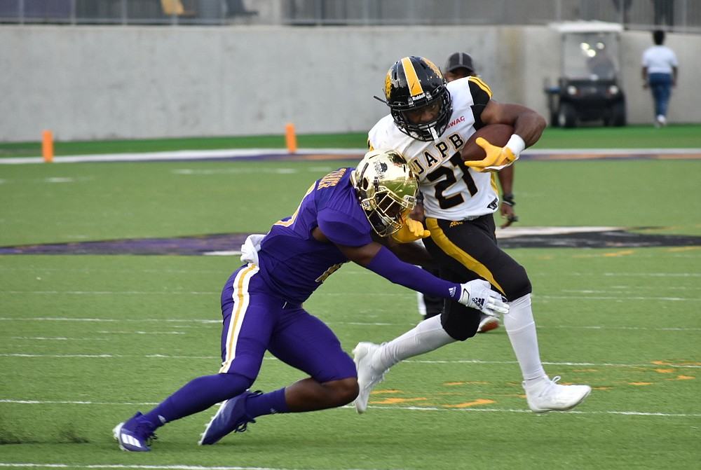 UAPB running back Kierre Crossley tries to break a tackle by Prairie View A&M strong safety Bryce Turner in the first quarter Thursday in Prairie View, Texas. (Pine Bluff Commercial/I.C. Murrell)
