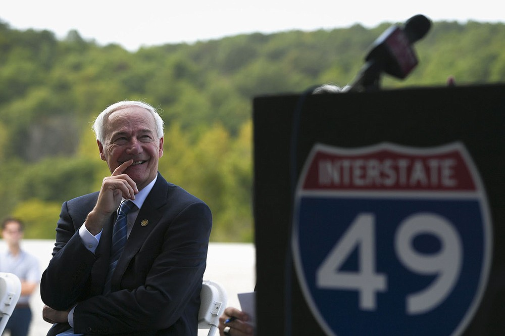 Gov. Asa Hutchinson smiles as he listens to Missouri Gov. Mike Parson speak (not pictured), Thursday, September 30, 2021 along the new Interstate 49 Bella Vista Bypass near Hiwasse. Arkansas Gov. Asa Hutchinson and Missouri Gov. Mike Parson joined highway officials from both states, highway commissioners, legislators and members of the public at the Arkansas-Missouri border to celebrate with a ribbon cutting. The newly constructed highway will open to the public Friday. Check out nwaonline.com/211001Daily/ for today's photo gallery.  (NWA Democrat-Gazette/Charlie Kaijo)
