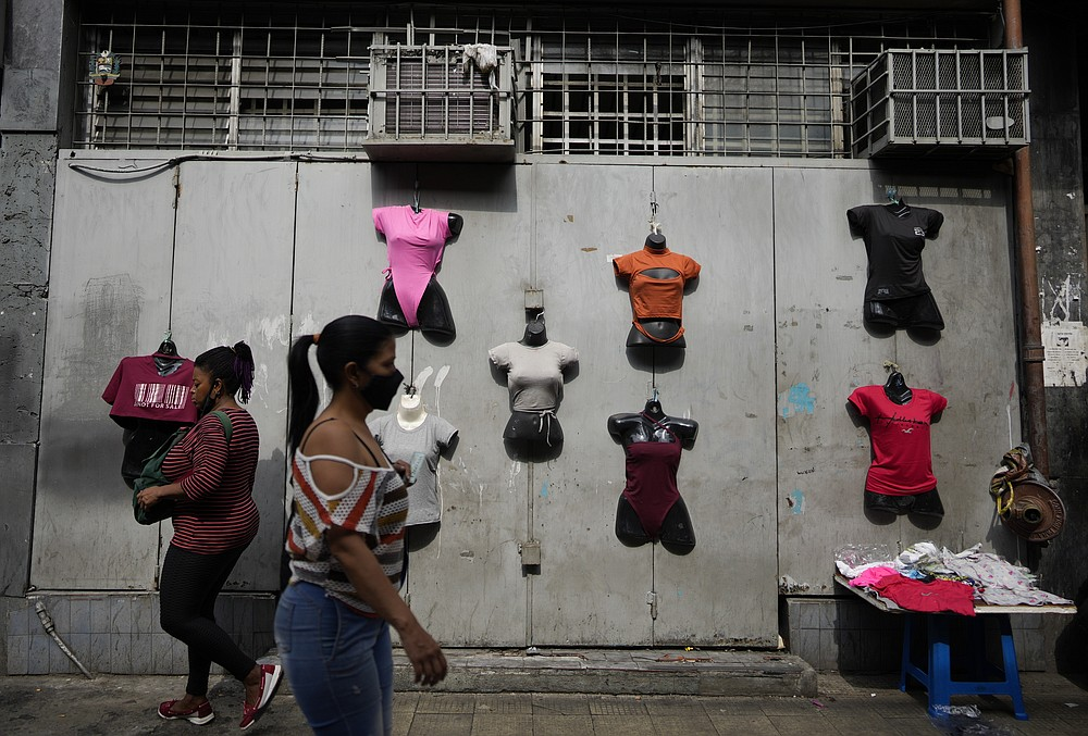 Residents walk past mannequins displaying women's clothes for sale in Caracas, Venezuela, Friday, Oct 1, 2021. A new currency with six fewer zeros debuts today in Venezuela, whose currency has been made nearly worthless by years of the world's worst inflation. The new currency tops out at 100 bolivars, a little less than $25 until inflation starts to eat away at that as well. (AP Photo/Ariana Cubillos)