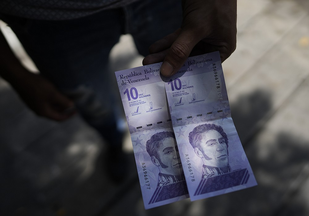 A man shows a new 10 Bolivar bank note after withdrawing it from a cash machine in Caracas, Venezuela, Friday, Oct 1, 2021. A new currency with six fewer zeros debuts Friday in Venezuela, whose currency has been made nearly worthless by years of the world's worst inflation. The new currency tops out at 100 bolivars, a little less than $25 until inflation starts to eat away at that as well. (AP Photo/Ariana Cubillos)