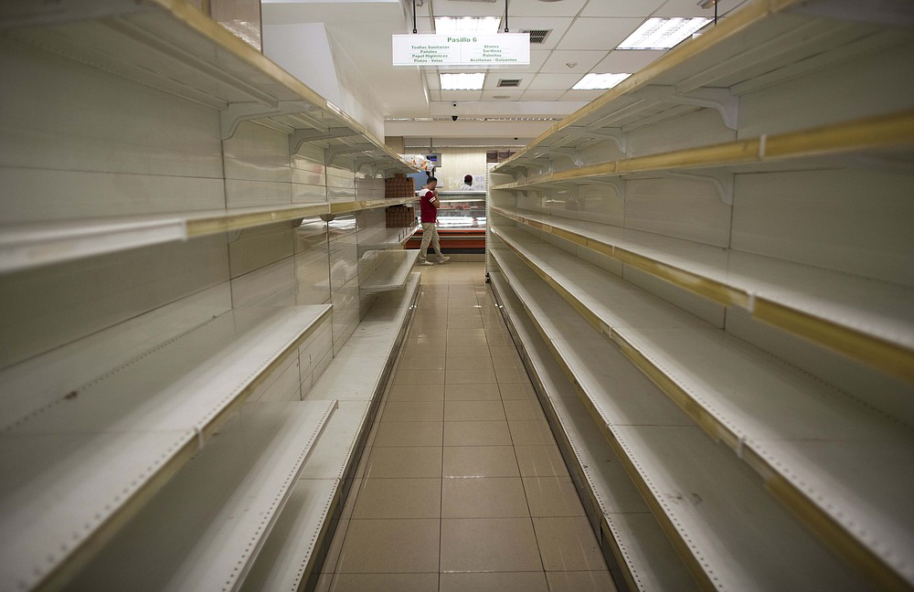 FILE - In this March 23, 2018 file photo, empty shelves stand in a supermarket in Caracas, Venezuela. A new currency with six fewer zeros debuts Friday, Oct. 1, 2021, in Venezuela, whose currency has been made nearly worthless by years of the world's worst inflation. (AP Photo/Ariana Cubillos, File)