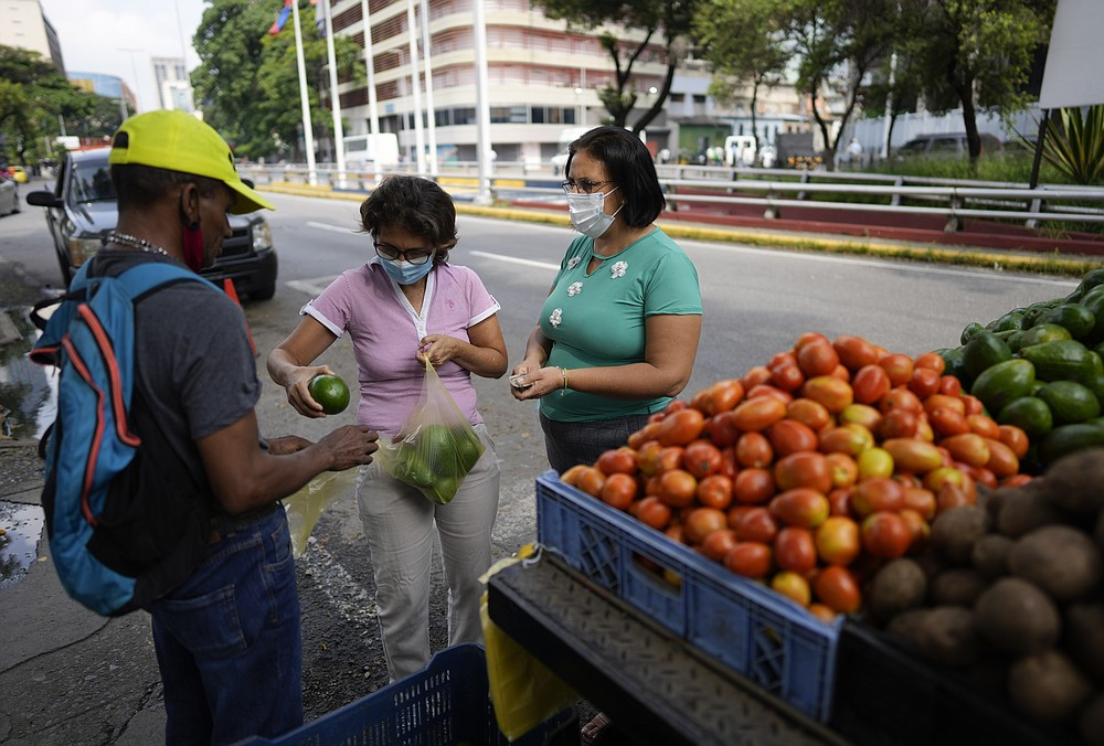 A woman purchases avocados from a produce vendor in Caracas, Venezuela, Friday, Oct 1, 2021. A new currency with six fewer zeros debuts today in Venezuela, whose currency has been made nearly worthless by years of the world's worst inflation. The new currency tops out at 100 bolivars, a little less than $25 until inflation starts to eat away at that as well. (AP Photo/Ariana Cubillos)