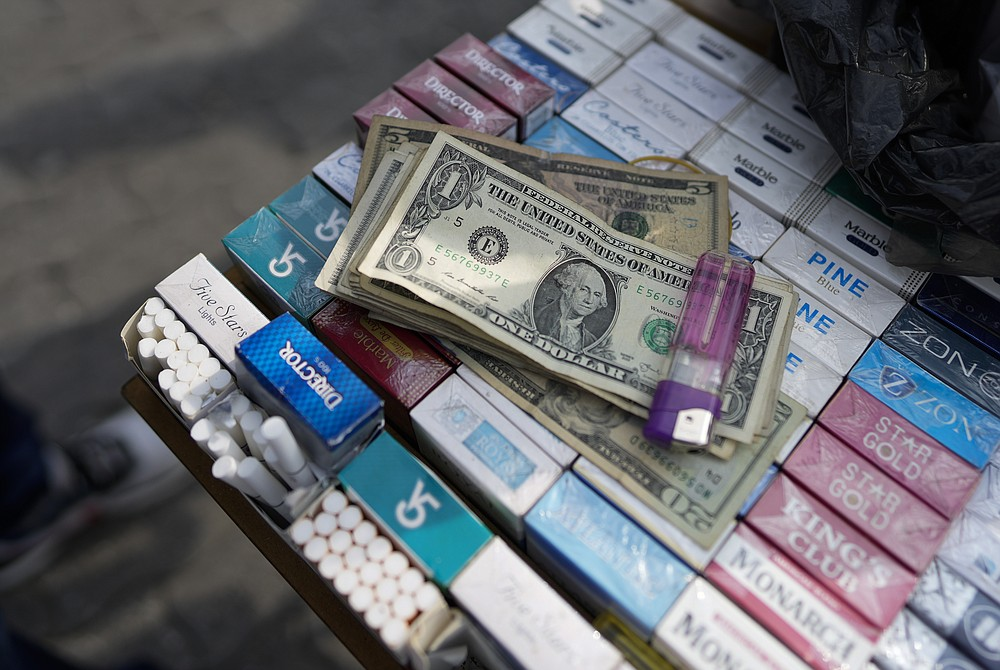 U.S. dollar bills, belonging to a street vendor, sit atop cigarettes for sale in Caracas, Venezuela, Friday, Oct. 1, 2021. A new currency with six fewer zeros debuts today in Venezuela, whose currency has been made nearly worthless by years of the world's worst inflation. The new currency tops out at 100 bolivars, a little less than $25 until inflation starts to eat away at that as well. (AP Photo/Ariana Cubillos)