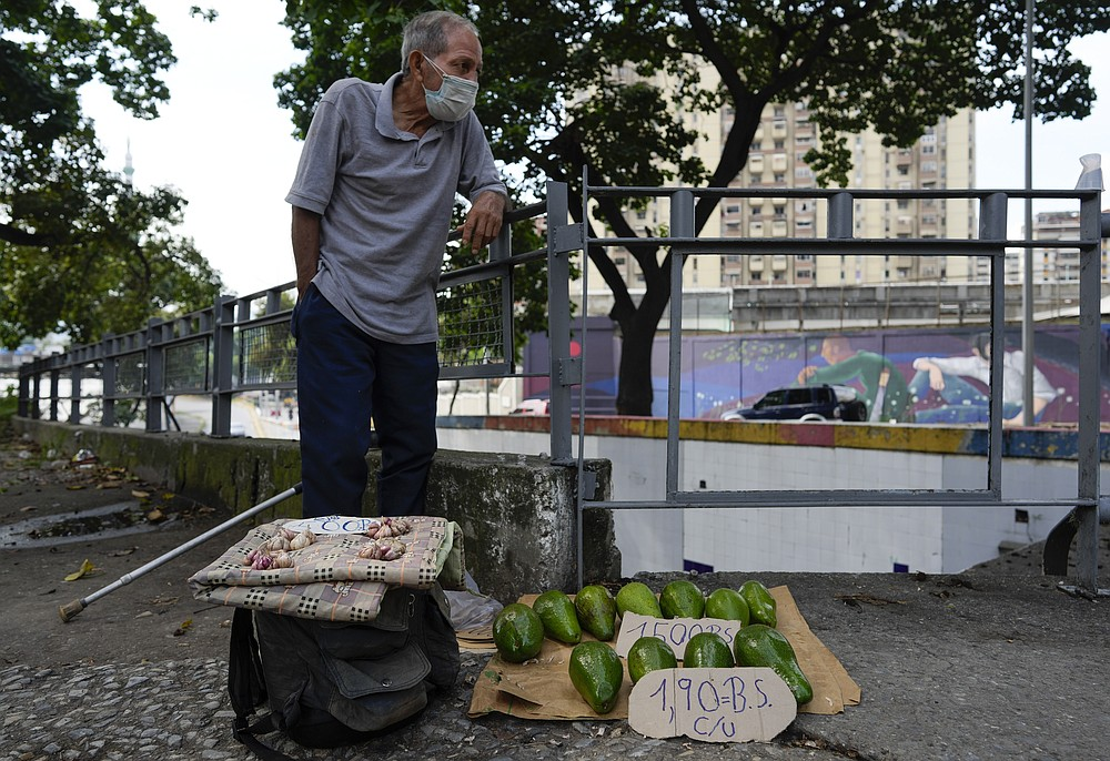 Rafael Rojas sell avocados and garlic on a street in Caracas, Venezuela, Friday, Oct 1, 2021. A new currency with six fewer zeros debuts today in Venezuela, whose currency has been made nearly worthless by years of the world's worst inflation. The new currency tops out at 100 bolivars, a little less than $25 until inflation starts to eat away at that as well. (AP Photo/Ariana Cubillos)