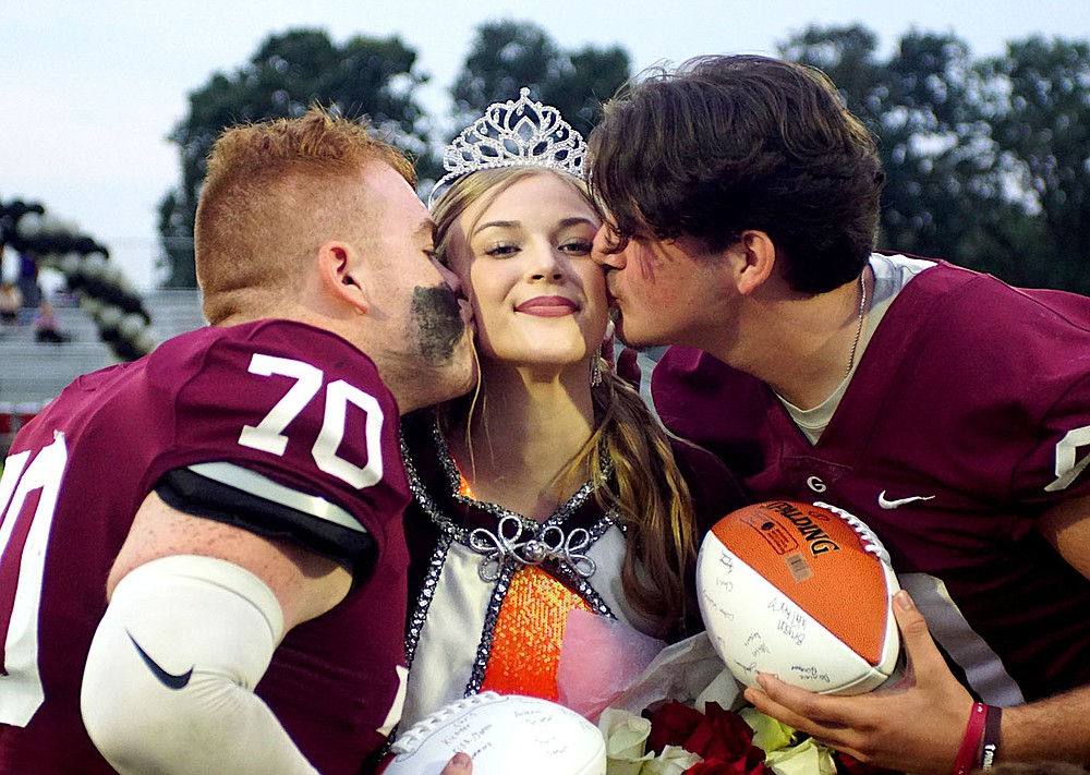 Westside Eagle Observer/RANDY MOLL Gentry's homecoming queen, Cora Bass, was kissed by homecoming captains Isaiah Freeman and Garrison Jackson during ceremonies in Pioneer Stadium at Gentry High School on Friday night.