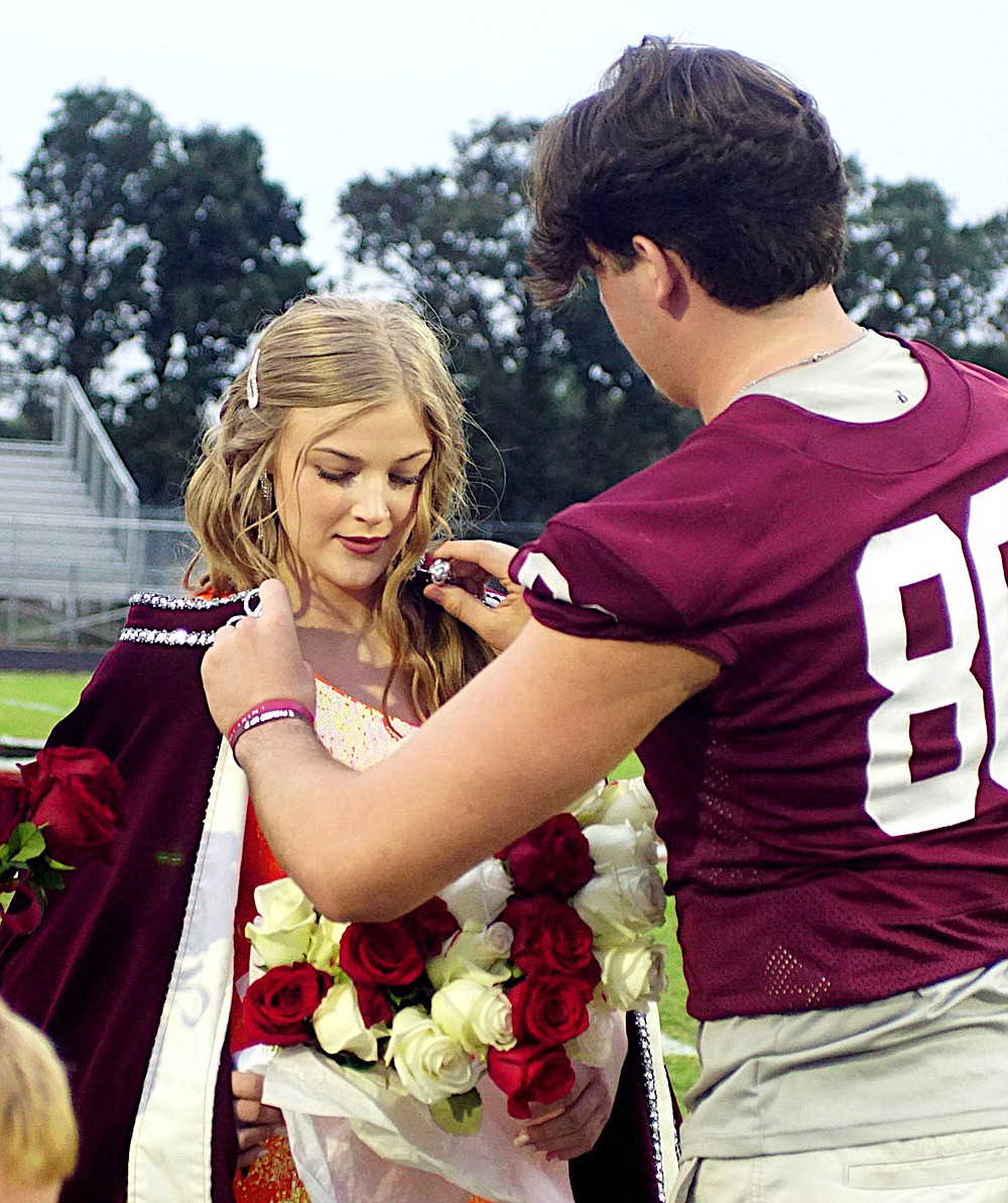 Westside Eagle Observer/RANDY MOLL Gentry homecoming king Garrison Jackson places the royal robe on Gentry's homecoming queen, Cora Bass, during ceremonies in Pioneer Stadium on Friday night.