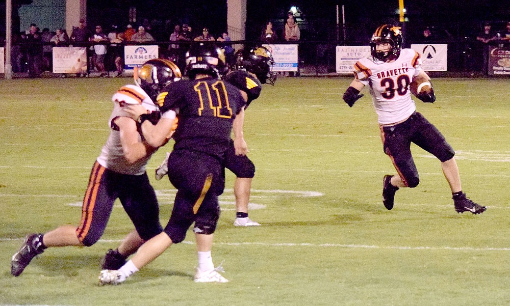 Westside Eagle Observer/MIKE ECKELS Kyler Austin (Gravette 30) runs around several blocks on his way to one of three touchdowns he had for the Lions during the Prairie Grove-Gravette football contest Oct.1. The Lions squared off against the Eagles in Huntsville Friday night. Huntsville won the conference game 41-19 over Gravette.