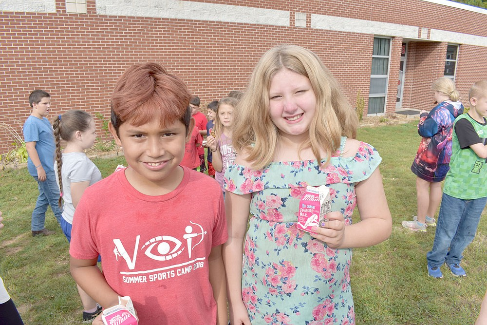 RACHEL DICKERSON/MCDONALD COUNTY PRESS Esteban Perez, left, and Bre Shoemaker enjoy strawberry milk along with their fellow fourth graders at Anderson Elementary School. The two students circulated a petition that inspired the food service company to bring strawberry milk back to the school district.